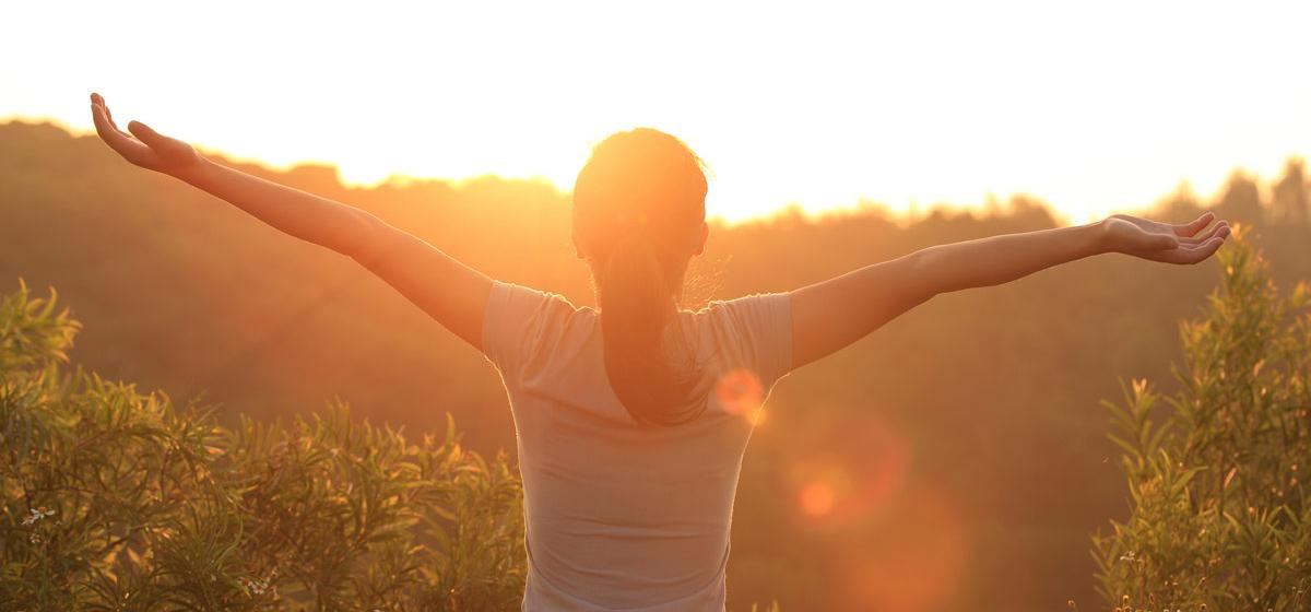 Healthy Woman at Sunrise with Outstretched Arms